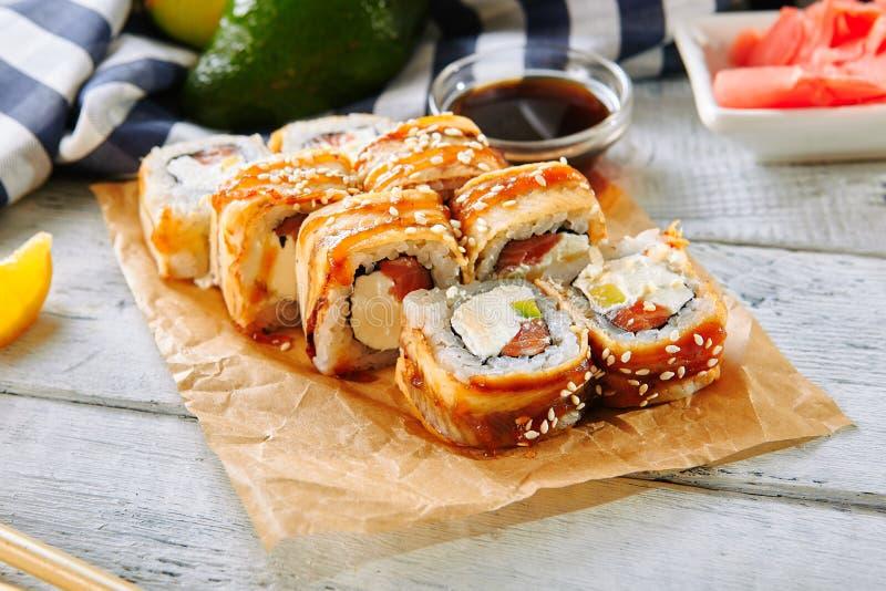Salmon and Smoked Eel Sushi Roll. With Pickled Daikon, Sauce, Sesame Close Up. Macro Photo of Nori Maki, Norimaki or Futomaki with Unagi and Raw Fish, Seaweed royalty free stock images