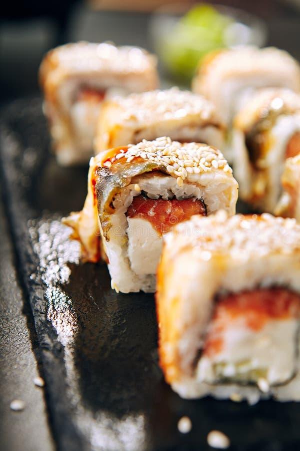 Salmon and Smoked Eel Sushi Roll. With Sauce and Sesame Close Up. Macro Photo of Nori Maki, Norimaki or Futomaki with Unagi and Raw Fish, Seaweed on Black Slate stock image