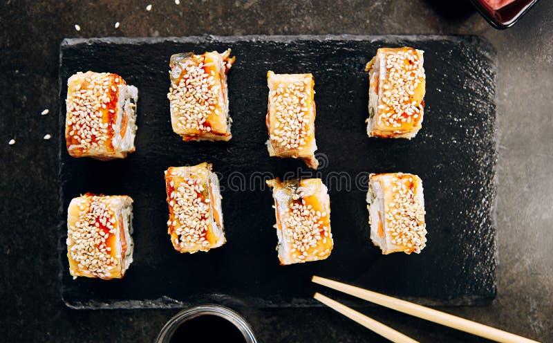 Salmon and Smoked Eel Sushi Roll. With Sauce and Sesame Top View. Top View  of Nori Maki, Norimaki or Futomaki with Unagi and Raw Fish, Seaweed on Black Slate stock image