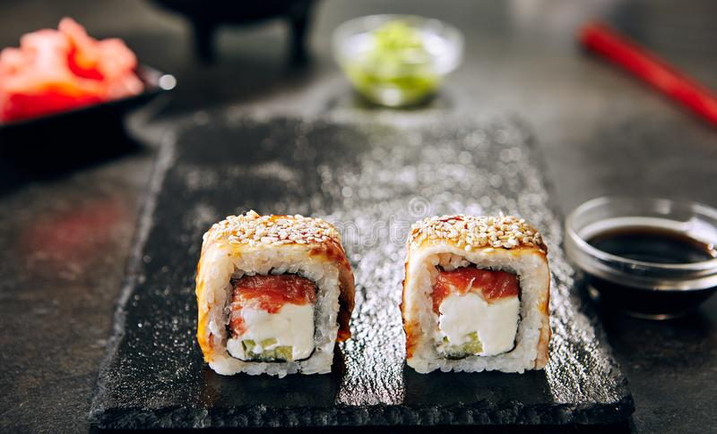 Salmon and Smoked Eel Sushi Roll. With Sauce and Sesame Close Up. Macro Photo Nori Maki, Norimaki or Futomaki with Unagi and Raw Fish, Seaweed on Black Slate stock images