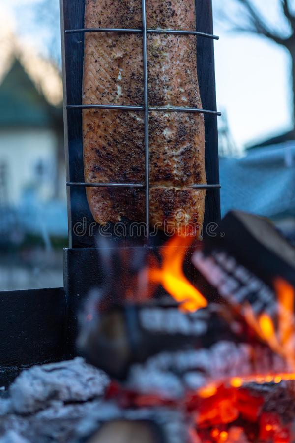 Salmon is smoked on open fire. / salmon on fire stock photography