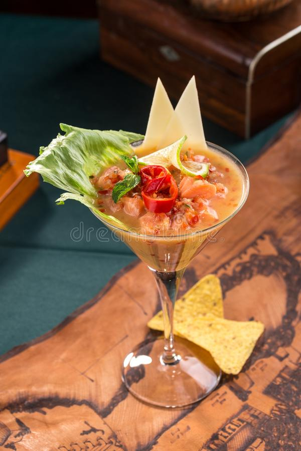 Salmon snack or tartar with chili pepper and nachos in martini glass on old map background royalty free stock photo