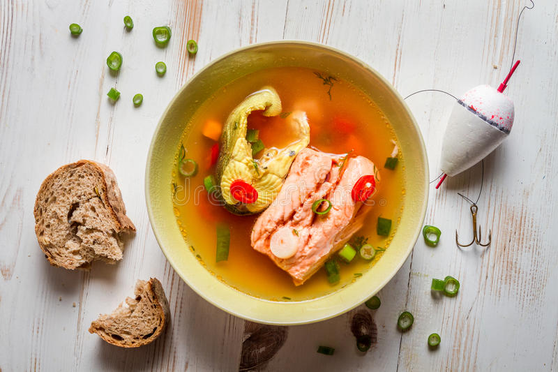 Salmon soup served with bread. On old wooden table royalty free stock image