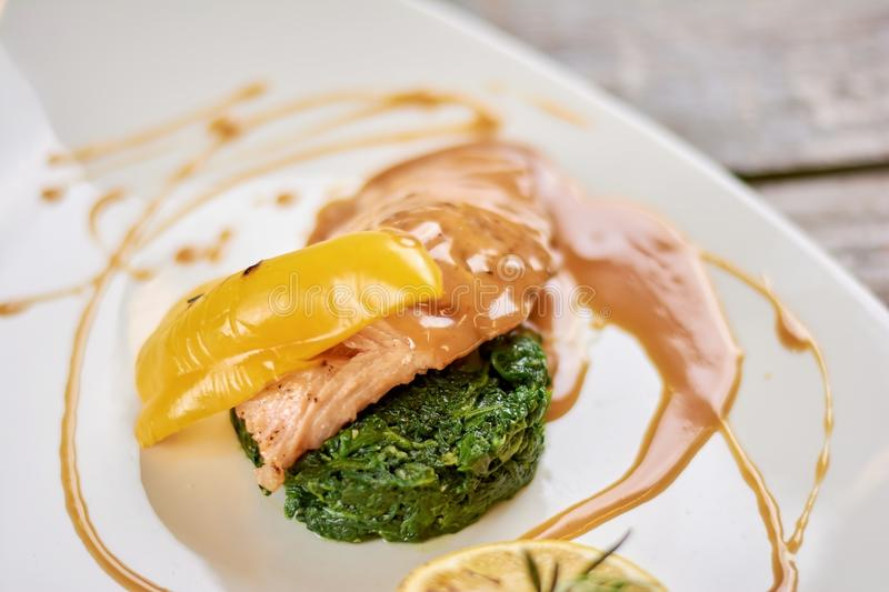 Salmon with soy caramel sauce. Delicious salmon with garnishing and sweet sauce. Appetizing dish at restaurant close up stock image