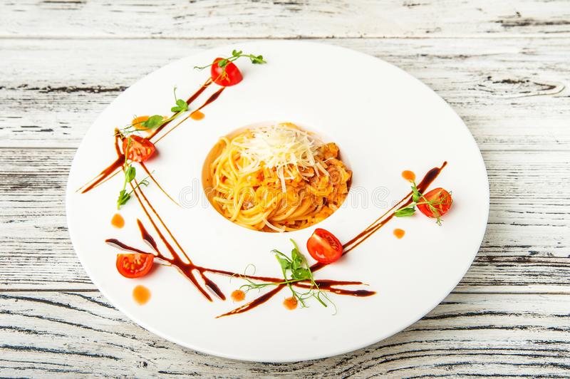Salmon spaghetti in creamy tomato sauce on a white plate. Traditional Italian pasta with sauce, tomatoes and basil close-up and co stock photos