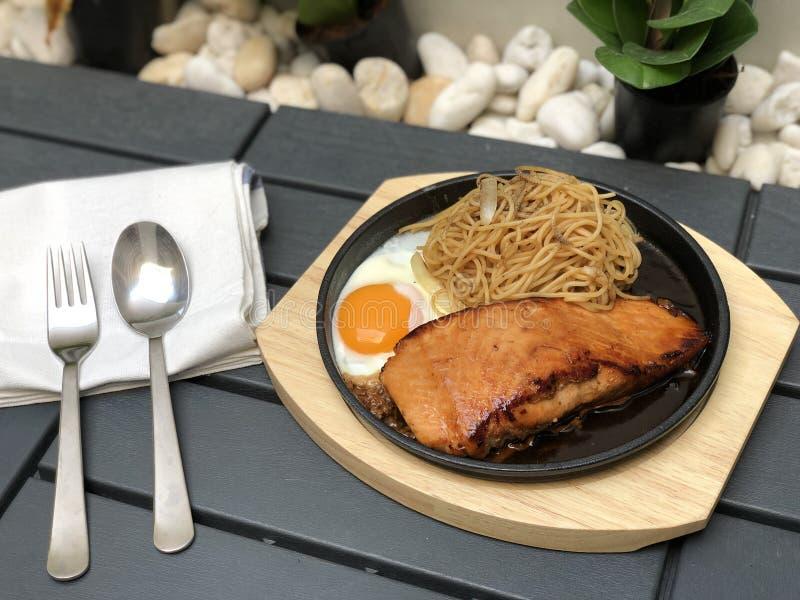 Salmon Steak as? a la parrilla con los tallarines de los espaguetis sazona la cebolla en la cacerola caliente y el plato de mader foto de archivo