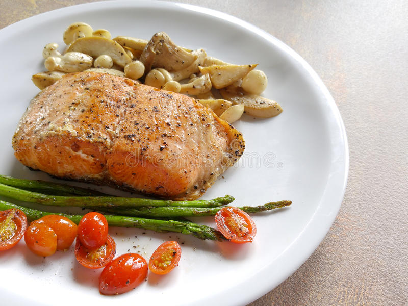 Salmon steak with asparagus, tomato and mushroom. stock photos