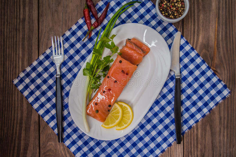 Salmon steak, butter, pepper, lemon and greens on a plate wooden rustic background. close-up. stock photography