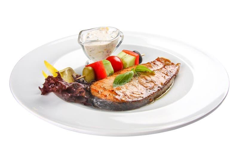 Salmon Steak con las verduras y la salsa En un fondo blanco imagenes de archivo