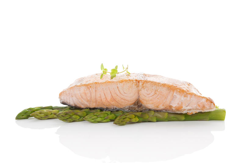 Salmon steak. Delicious salmon steak on green asparagus on white background. Culinary seafood eating royalty free stock photos