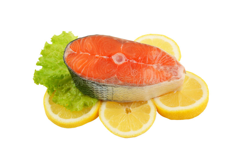 Salmon steak with greens and lemon royalty free stock photography