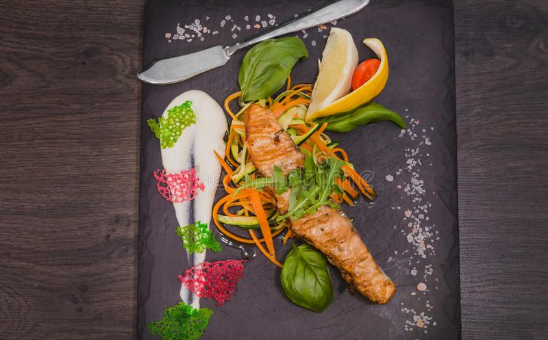 Salmon steak with lemon greens and sauce on stone with salt stock photo