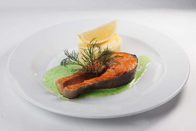 Salmon Steak with mashed potatoes on a plate isolated white background pesto stock photos