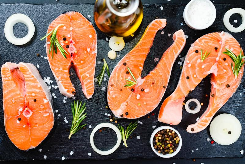 Salmon steak, pepper and salt, herbs on black stone concrete table, copy space top view. Two salmon steak, butter, pepper and salt, lemon, herbs border ,place royalty free stock photos