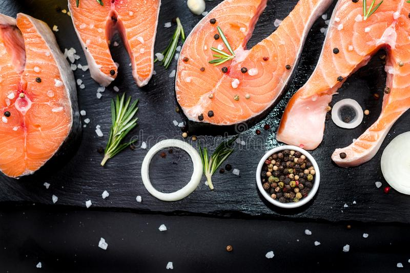 Salmon steak, pepper and salt, herbs on black stone concrete table, copy space top view. Two salmon steak, butter, pepper and salt, lemon, herbs border ,place royalty free stock photography