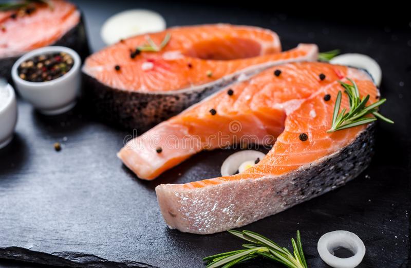 salmon steak, pepper and salt, herbs on black stone concrete table, copy space top view stock photography