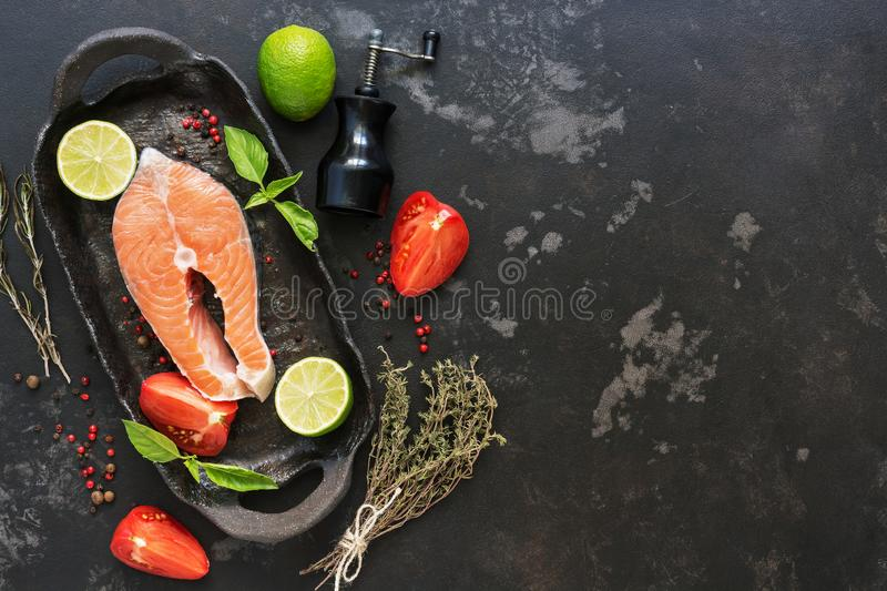 Salmon steak raw with ingredients for cooking on a black stone background. Top view, copy space. stock image