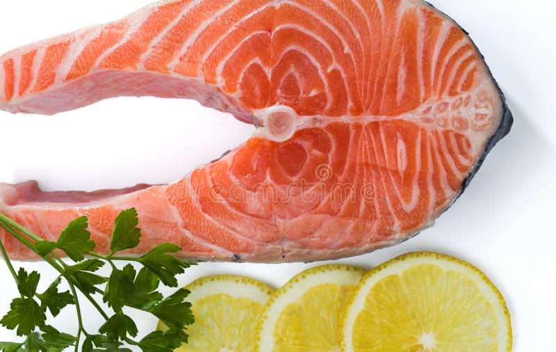 Salmon steak with a sprig of parsley and three lemon slices isolated on white stock photo