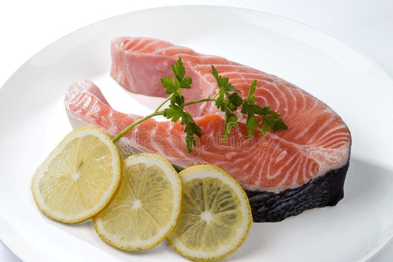 Salmon steak with a sprig of parsley and three lemon slices on a white plate royalty free stock photos