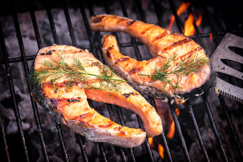 Salmon steaks cooking on barbecue grill for summer outdoor party royalty free stock photography