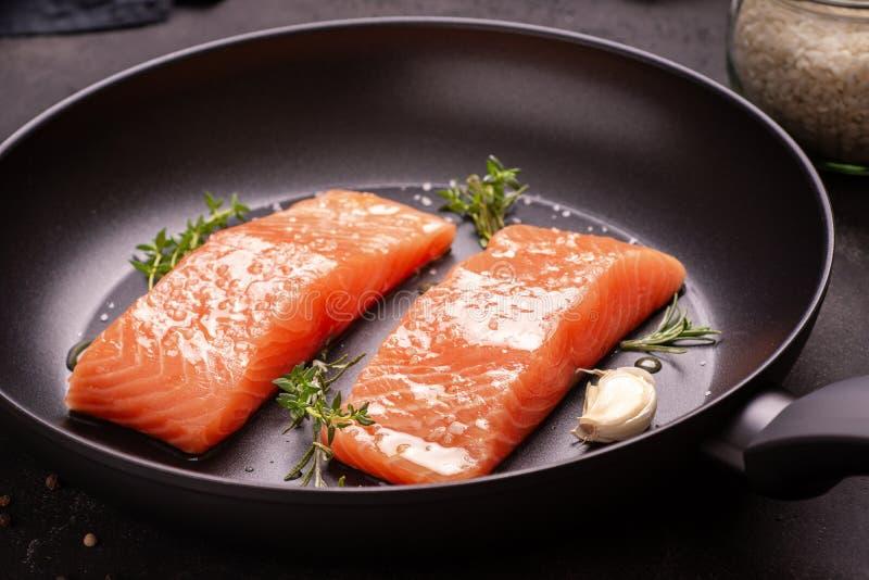 Salmon Steaks fresco y crudo en sart?n con tomillo y ajo foto de archivo