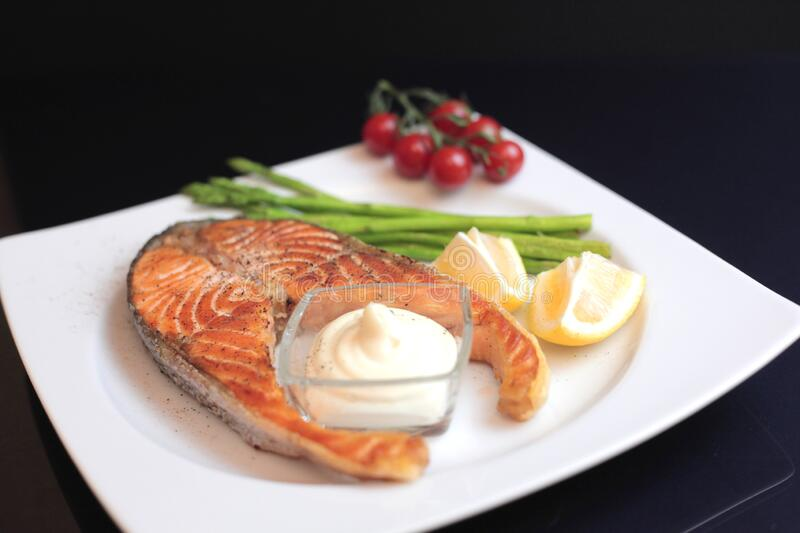 salmon steaks with vegetables and spices: asparagus, tomatoes, ginger, pepper corns, salt, chili, onion, lemon and olive oil on stock image
