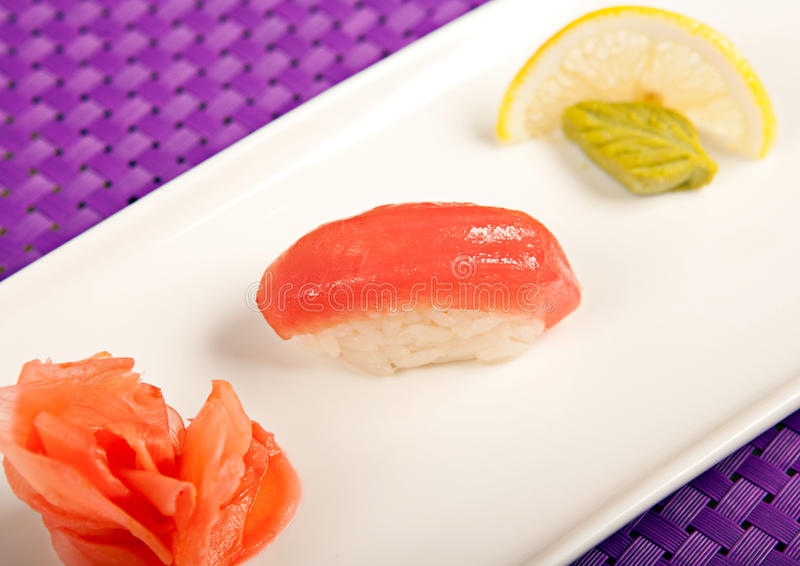 Salmon sushi on the plate, lemon, wasabi and ginger royalty free stock photography