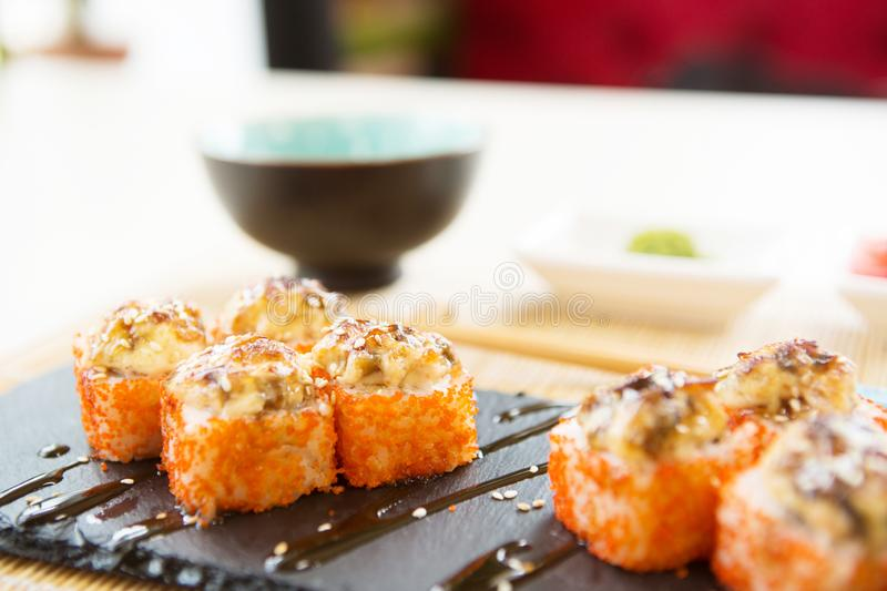 Salmon sushi roll - japanese food style. Fried hot Roll with salmon, avocado, cucumber royalty free stock photos