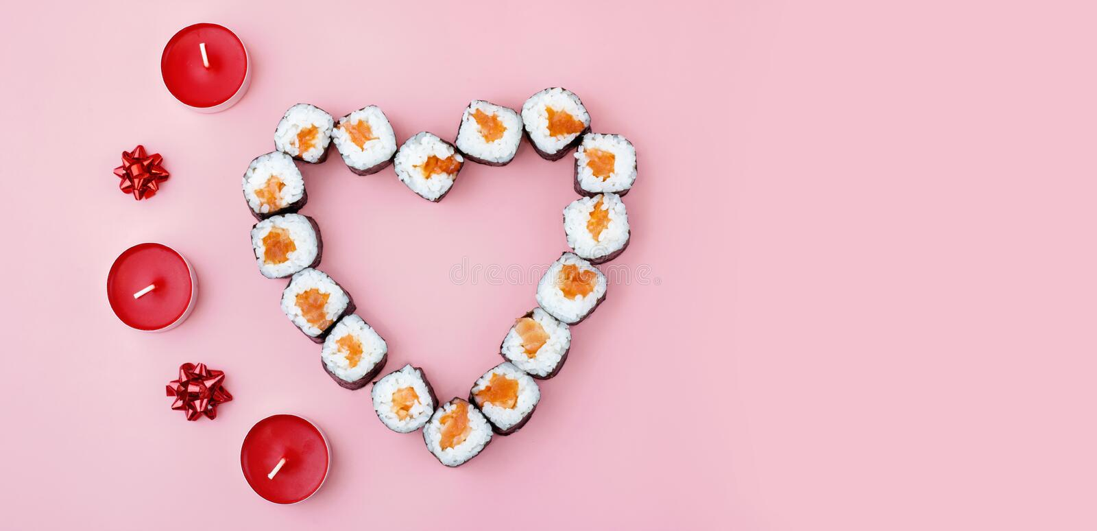 Salmon sushi rolls laid out in the shape of a heart, next to red candles and bowson a pink background. The concept of Japanese royalty free stock photo