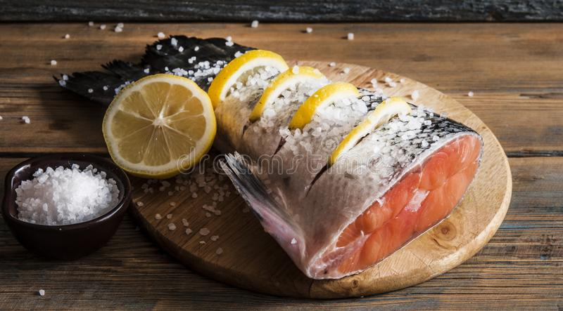 Salmon tail with lemon and  sea salt on wooden table stock image