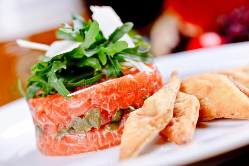 Salmon tartare with capers, arugula salad and parmesan cheese. On white plate stock image