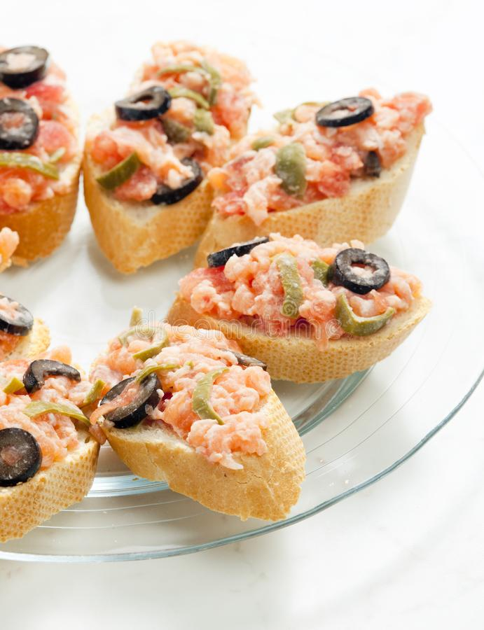 Salmon tartare with capers and black olives. Inside, indoor, indoors, interior, interiors, gastronomy, cuisine, foodstuff, aliment, aliments, meal, meals stock photo