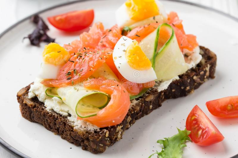 Salmon toast with cream cheese, cucumber and egg. Delicious lunch, healthy food, fish sandwich, diet snack. Salmon toast with cream cheese, cucumber egg stock photography