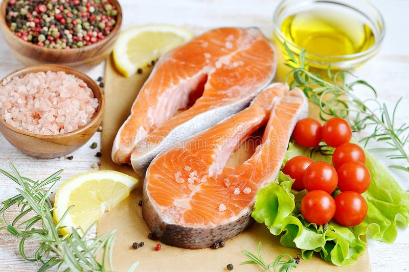 Salmon Trout Fish Cooking Raw Fillet Pepper Salt Olive Oil Rosemary Lemon Green Tomato Salad Wooden Table Lifestyle Healthy Concep royalty free stock photo