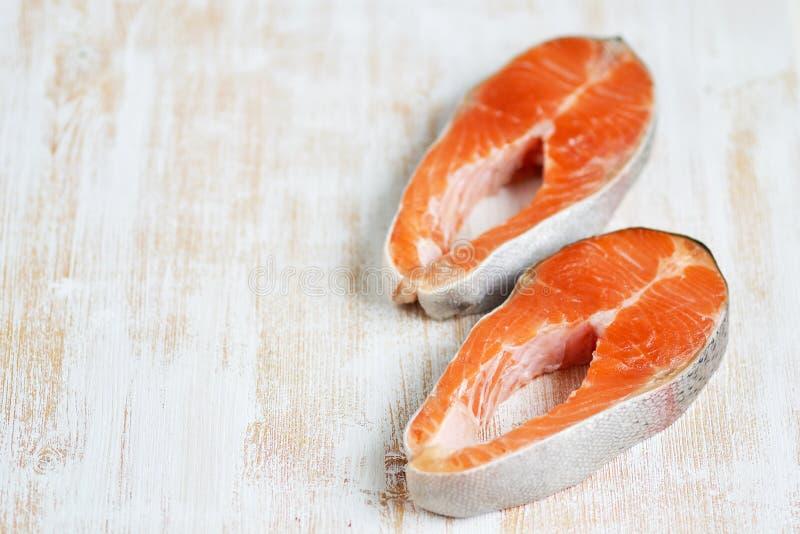 Salmon Trout Fish Cooking Raw-Leisten-Pfeffer-Salz-Olive Oil Rosemary Lemon Green-Tomaten-Salat-Holztisch-Lebensstil gesundes Con lizenzfreies stockfoto