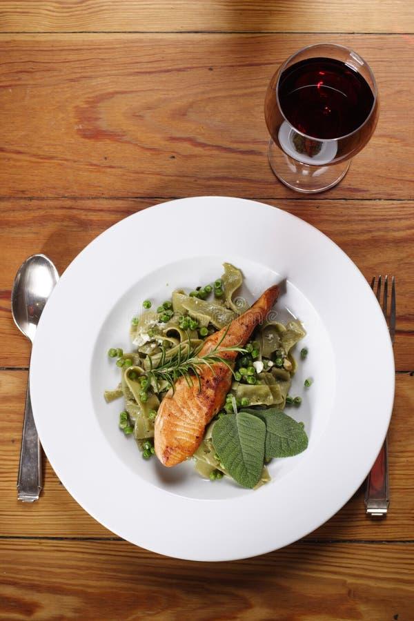 Salmon with wild garlic pasta stock images