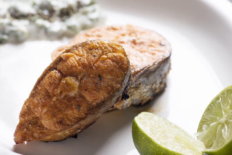 Salmone arrostito con il limone e l'insalata fotografia stock