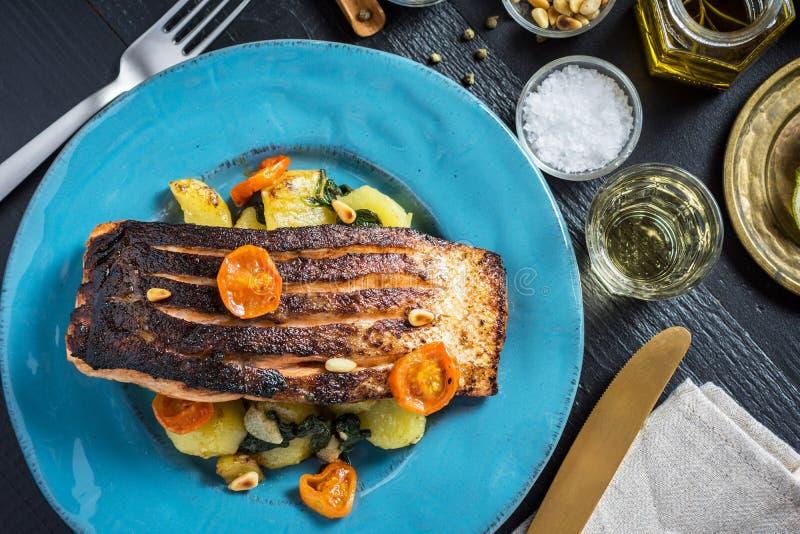 Salmone arrostito con le verdure servite sul piatto blu fotografia stock