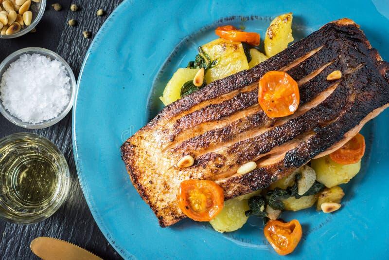 Salmone arrostito con le verdure servite sul piatto blu fotografia stock libera da diritti