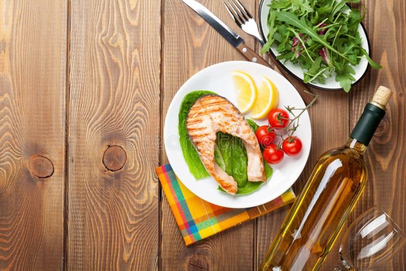 Salmone arrostito e vino bianco sulla tavola di legno immagini stock libere da diritti