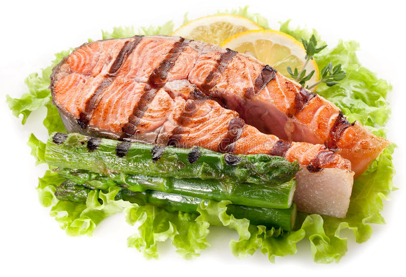 Salmone arrostito ed asparago su un fondo bianco. immagine stock