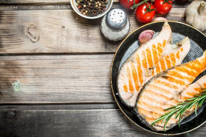 Salmone arrostito in una pentola con le spezie e le erbe fotografia stock libera da diritti