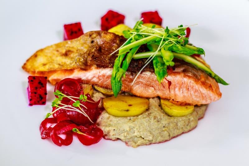 Salmone atlantico pelato croccante con asparago sauteed, la patata arrostita e il ghanouch del babza fotografia stock libera da diritti