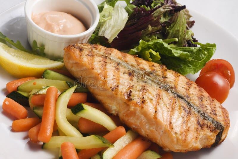 Salmone con le verdure fritte ed il pomodoro fresco immagine stock