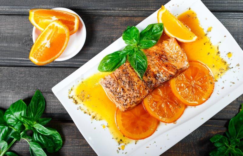 Salmone del raccordo di Honey Glazed con le fette, le spezie ed il basilico arancio sul piatto bianco su fondo scuro fotografia stock libera da diritti