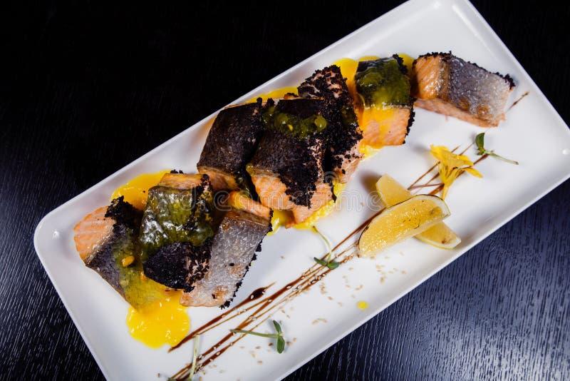 Salmone del raccordo di Honey Glazed con le fette, le spezie ed il basilico arancio sul piatto bianco su fondo scuro fotografia stock