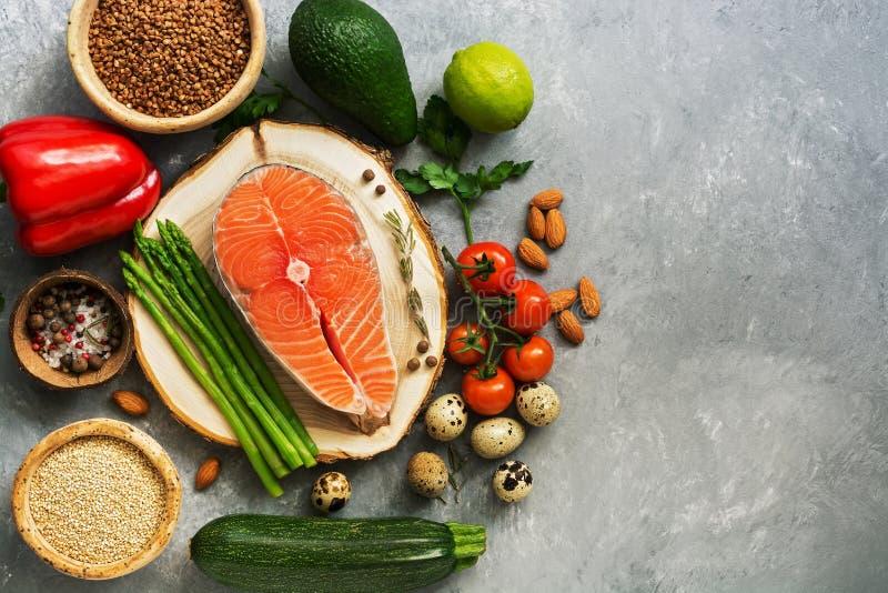 Salmone del trancio di pesce, cereali, ortaggi freschi, uovo di quaglia, dadi e spezie crudi su un fondo grigio Nutrizione equili fotografia stock