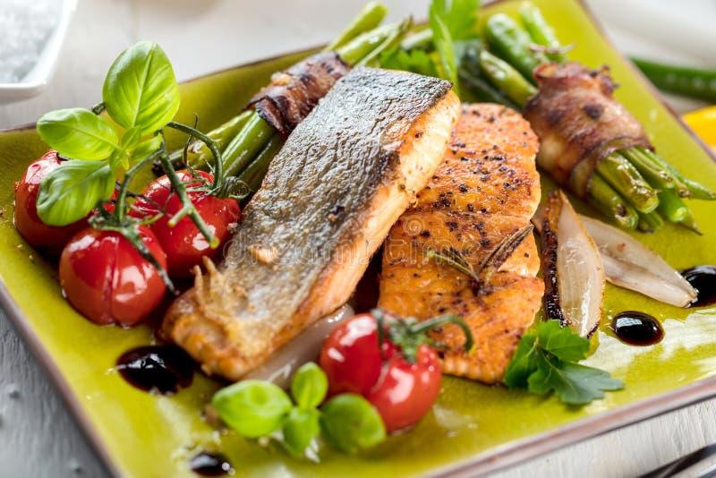 Salmone grigliato con le verdure servite sul piatto di pietra verde sulla tavola di legno immagini stock libere da diritti