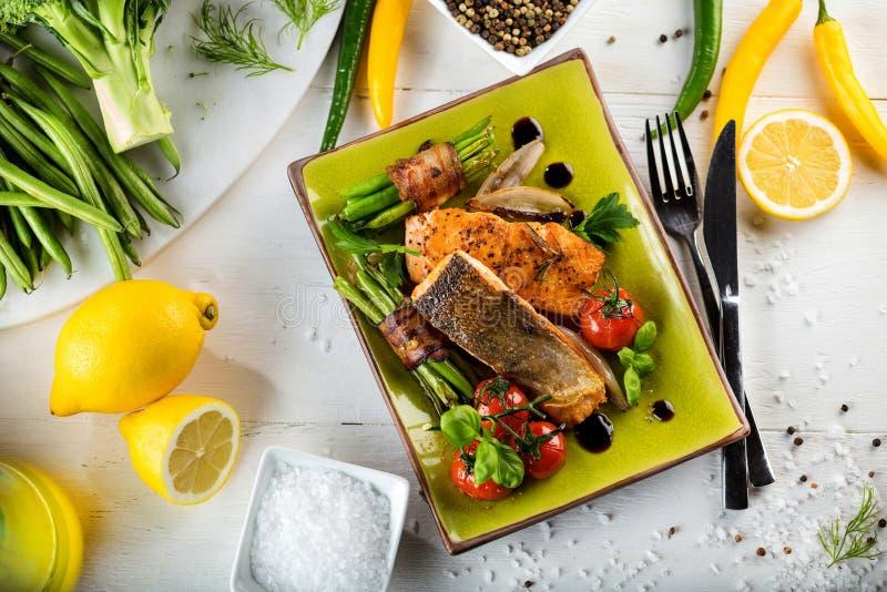 Salmone grigliato con le verdure servite sul piatto di pietra verde sulla tavola di legno fotografie stock libere da diritti