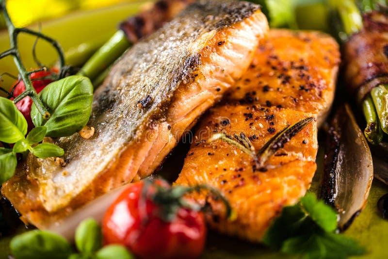 Salmone grigliato con le verdure servite sul piatto di pietra verde sulla tavola di legno immagini stock